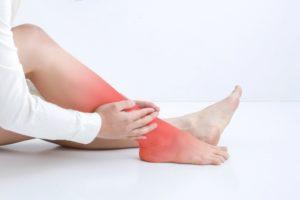 痛い足を抑える女性