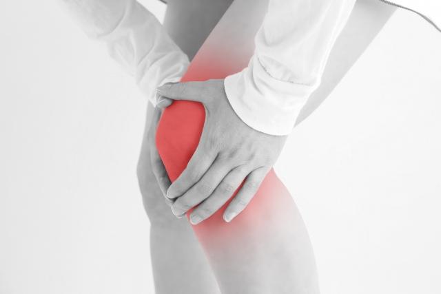 痛みで膝を押さえる