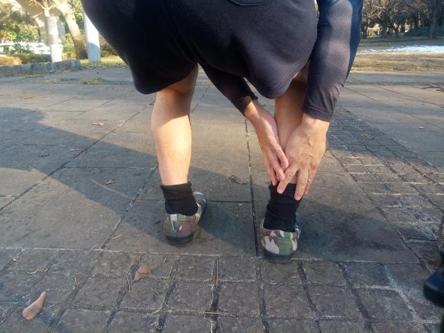 アキレス腱部を抑える男性