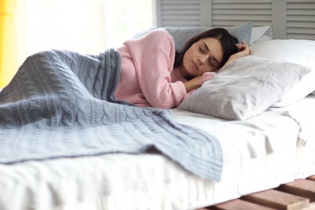 ベッドで気持ちよさそうに眠る女性