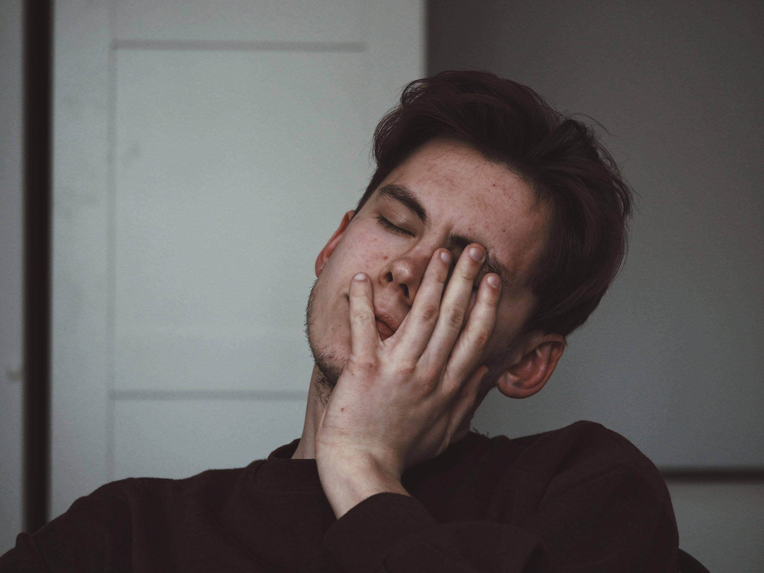 頭痛でうなだれる男性