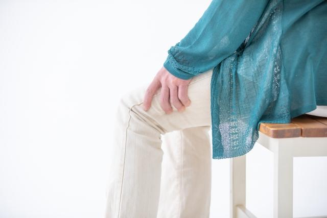 膝が痛くてさする女性
