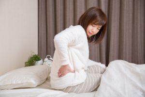 起床時の腰の痛みを訴える女性