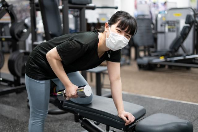 マスクを着けてダンベルトレーニングする女性
