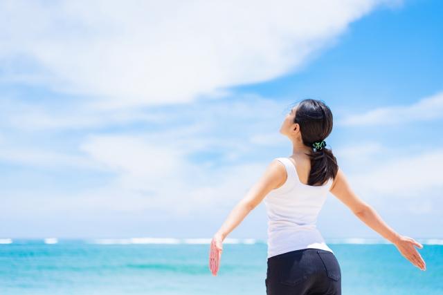 生き生きと青空に向かって手を広げる女性